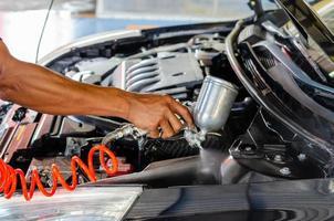 Gros plan d'une personne détaillant l'intérieur du moteur de la voiture photo