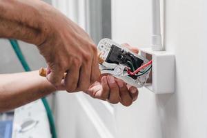 électricien installe une prise électrique photo