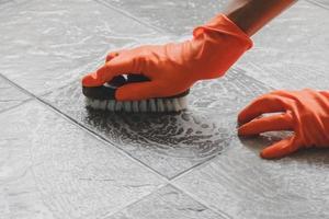 personne frottant un sol avec des gants orange sur photo