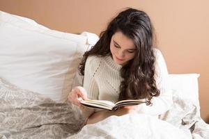jeune femme, lecture livre, dans lit photo