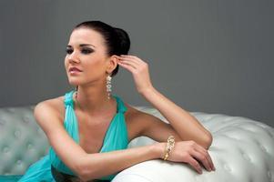 fille dans une robe turquoise allongée sur le canapé