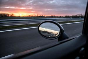 Vue depuis la fenêtre d'une voiture en conduisant au coucher du soleil photo