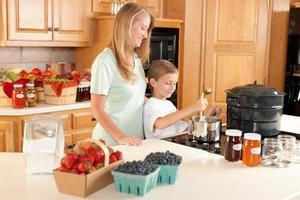 mise en conserve: mère fils préparant des conserves maison à partir de fruits et légumes du cru photo