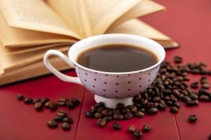 Tasse de café avec des grains de café isolé sur fond rouge photo