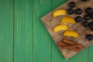 Assortiment de fruits sur une planche à découper sur fond vert