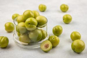 Prunes vertes en pot et sur fond blanc