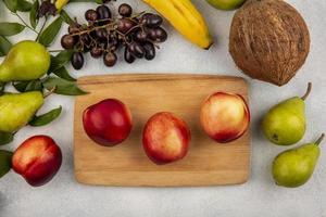 Assortiment de fruits sur une planche à découper et fond neutre