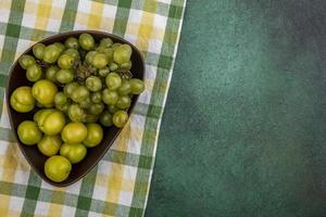 Fruits verts dans un bol sur tissu à carreaux et fond vert
