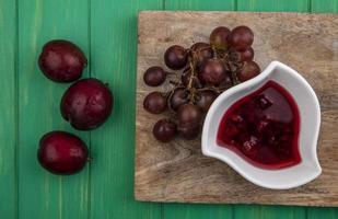 Fruits frais avec de la confiture de framboises sur une planche à découper sur fond vert photo