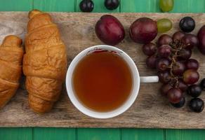 tasse de thé avec des croissants et des baies sur une planche à découper