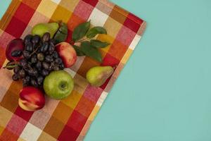 Fruits assortis sur tissu à carreaux et fond bleu