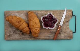 Croissants et confiture de framboises avec couteau sur planche à découper sur fond bleu