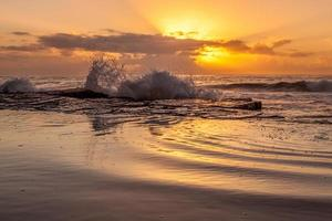 vagues de l'océan s'écraser sur le rivage pendant le coucher du soleil