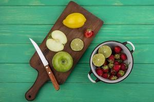 Assortiment de fruits sur une planche à découper sur fond de bois vert