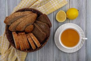 Tranches de pain et de thé sur fond de bois photo