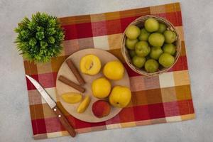 Assortiment de fruits sur nappe à carreaux sur fond blanc
