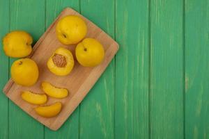 Tranches d'abricots sur une planche à découper sur fond vert avec espace copie