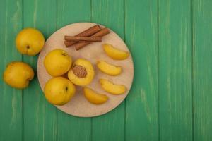Abricots à la cannelle sur une planche à découper sur fond vert avec espace copie photo