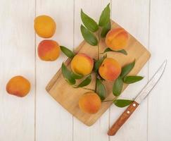 Abricots et feuilles sur une planche à découper sur fond de bois