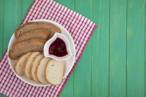 Tranches de pain avec de la confiture sur un tissu à carreaux sur fond vert photo