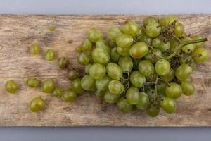 Raisins blancs sur une planche à découper sur fond gris photo