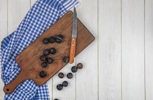 fruits noirs sur planche à découper et nappe à carreaux bleu photo