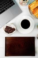 vue de dessus d'une tasse de café près d'un ordinateur portable