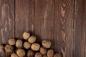 Vue de dessus de noix entières éparpillées sur fond de bois avec espace copie photo