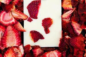 Vue de dessus d'une barre de chocolat blanc sur fond de tranches de fraises séchées