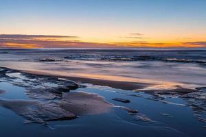 longue exposition d'un coucher de soleil sur une plage photo