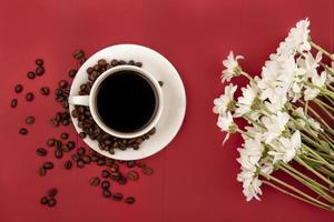 Vue de dessus du café sur une tasse blanche avec des grains de café sur fond rouge photo