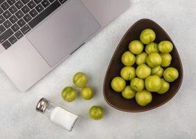 Vue de dessus des prunes dans un bol et sel avec carnet de notes sur fond blanc