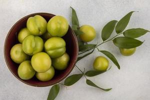 Vue de dessus des prunes vertes dans un bol avec des feuilles sur fond blanc