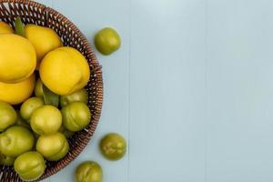 Vue de dessus des pêches jaunes fraîches avec des prunes cerises vertes photo
