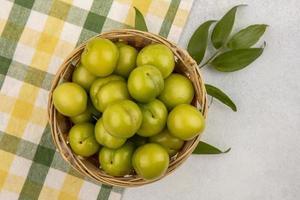 vue de dessus des prunes vertes dans le panier