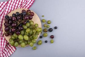 Vue de dessus des raisins sur une planche à découper sur tissu à carreaux et sur fond gris avec espace copie photo