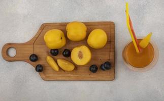 Vue de dessus des pêches jaunes fraîches sur une planche de cuisine en bois photo