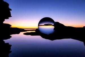 personne tenant une boule de verre au coucher du soleil