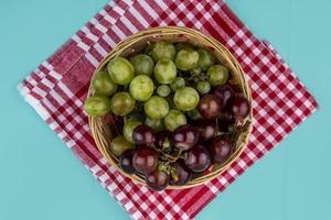 Vue de dessus des raisins dans le panier sur tissu à carreaux sur fond bleu