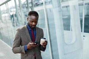 Homme lisant quelque chose dans son smartphone alors qu'il se tient dehors avec une tasse de café