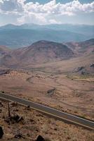 Route asphaltée grise près des montagnes brunes pendant la journée