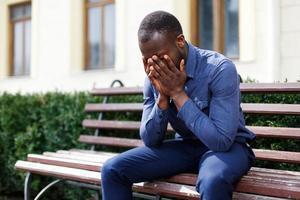 Homme afro-américain fatigué est assis sur le banc à l'extérieur photo