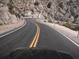 Route asphaltée noire près de la montagne rocheuse grise pendant la journée
