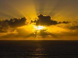 soleil couchant à travers les nuages sur l'océan
