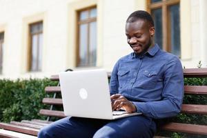 Heureux homme afro-américain travaille sur son ordinateur portable assis sur le banc à l'extérieur