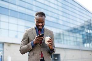 Heureux homme afro-américain lisant quelque chose dans son smartphone alors qu'il se tient à l'extérieur avec une tasse de café photo