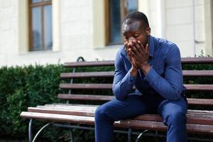 Homme afro-américain fatigué est assis sur le banc à l'extérieur