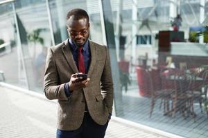 élégant homme d'affaires noir afro-américain travaille sur son smartphone