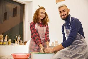 Beau couple souriant forme un vase dans un lieu de travail de poterie