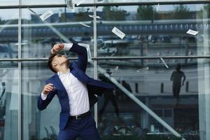 dollars volent autour de beau jeune homme d'affaires